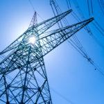 Sun shines through electricity pylon
