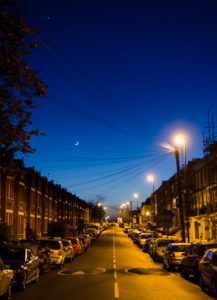 London, England, United Kingdom - April 20, 2015: The moon rises above traditional suburban terraced houses and parked cars in the Gipsy Hill neighbourhood of South London at night.